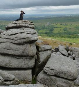 Person sitting on top of a huge granite rock
